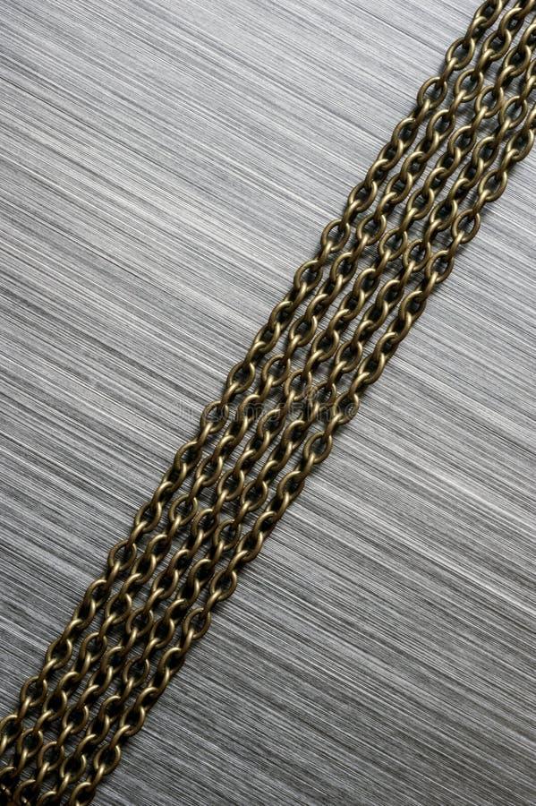 Αλυσίδες στο βουρτσισμένο υπόβαθρο μετάλλων στοκ φωτογραφίες με δικαίωμα ελεύθερης χρήσης