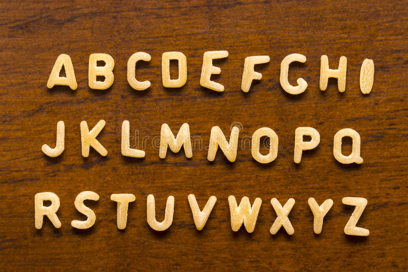 Αλφάβητο φιαγμένο από επιστολές μακαρονιών που απομονώνονται στο ξύλινο υπόβαθρο στοκ εικόνες
