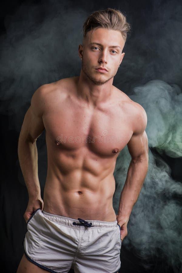 Αδύνατος αθλητικός νεαρός άνδρας γυμνοστήθων που στέκεται στο σκοτεινό υπόβαθρο στοκ φωτογραφία με δικαίωμα ελεύθερης χρήσης