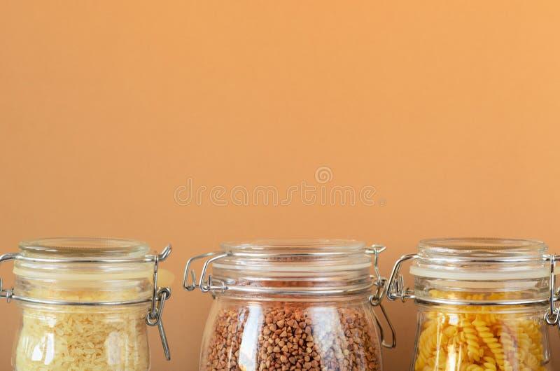Βάζα γυαλιού με τα άψητα δημητριακά, ζυμαρικά, ρύζι, φαγόπυρο σε ένα μπεζ υπόβαθρο Μηά έννοια αποβλήτων, ηλεκτρικοί οικιακοί εξοπ στοκ εικόνα