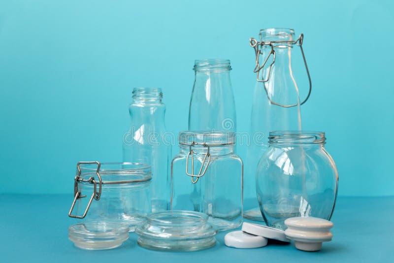 Βάζα γυαλιού που στέκονται στο μπλε υπόβαθρο Eco φιλικό, επαναχρησιμοποίηση ή μηά έννοια αποβλήτων στοκ εικόνα με δικαίωμα ελεύθερης χρήσης