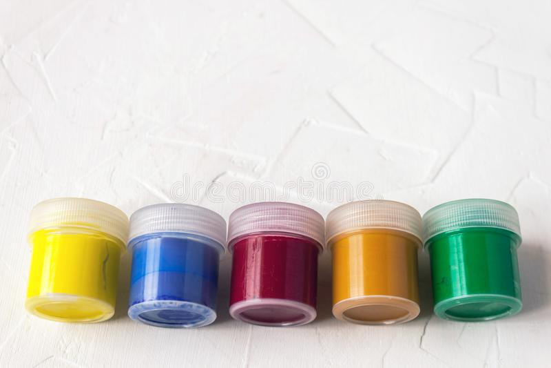 Βάζα με την πολύχρωμη γκουας ή ακρυλικά χρώματα σε ένα ελαφρύ άσπρο υπόβαθρο Εκλεκτικό μαλακό fokus Διάστημα αντιγράφων κειμένων στοκ εικόνες
