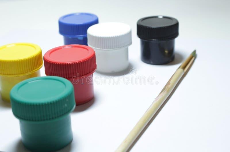 Βάζα με τις βούρτσες γκουας και χρωμάτων σε ένα άσπρο υπόβαθρο στοκ φωτογραφία με δικαίωμα ελεύθερης χρήσης