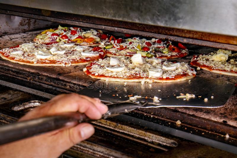 Βάζοντας την πίτσα στο φούρνο που ψήνεται στοκ εικόνες