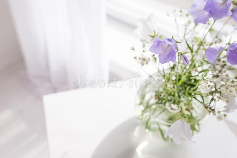 Βάζο γυαλιού με τα ιώδη και άσπρα floweers στο ελαφρύ άνετο εσωτερικό κρεβατοκάμαρων Άσπρος τοίχος, φως του ήλιου από το παράθυρο στοκ εικόνα με δικαίωμα ελεύθερης χρήσης