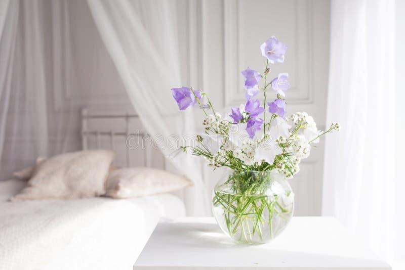 Βάζο γυαλιού με τα ιώδη και άσπρα floweers στο ελαφρύ άνετο εσωτερικό κρεβατοκάμαρων Άσπρος τοίχος, κρεβάτι με το άσπρο λινό, ελα στοκ φωτογραφίες με δικαίωμα ελεύθερης χρήσης