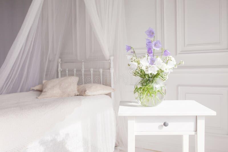 Βάζο γυαλιού με τα ιώδη και άσπρα floweers στο ελαφρύ άνετο εσωτερικό κρεβατοκάμαρων Άσπρος τοίχος, κρεβάτι με το άσπρο λινό, ελα στοκ φωτογραφία