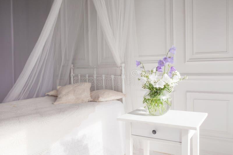 Βάζο γυαλιού με τα ιώδη και άσπρα floweers στο ελαφρύ άνετο εσωτερικό κρεβατοκάμαρων Άσπρος τοίχος, φως του ήλιου από το παράθυρο στοκ φωτογραφίες με δικαίωμα ελεύθερης χρήσης