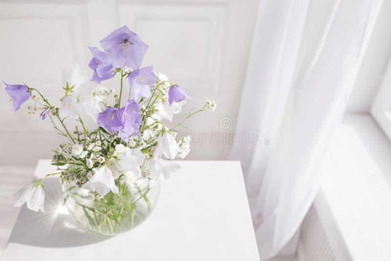 Βάζο γυαλιού με τα ιώδη και άσπρα floweers στο ελαφρύ άνετο εσωτερικό κρεβατοκάμαρων Άσπρος τοίχος, διάστημα αντιγράφων στοκ εικόνα