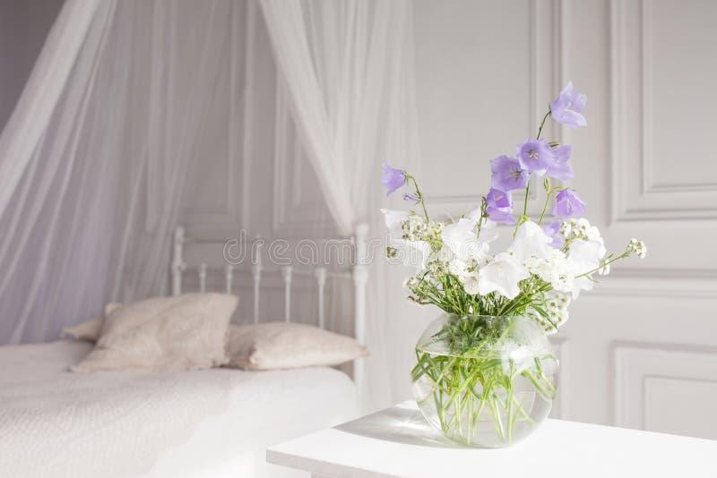 Βάζο γυαλιού με τα ιώδη και άσπρα floweers στο ελαφρύ άνετο εσωτερικό κρεβατοκάμαρων Άσπρος τοίχος, κρεβάτι με το άσπρο λινό, ελα στοκ εικόνα