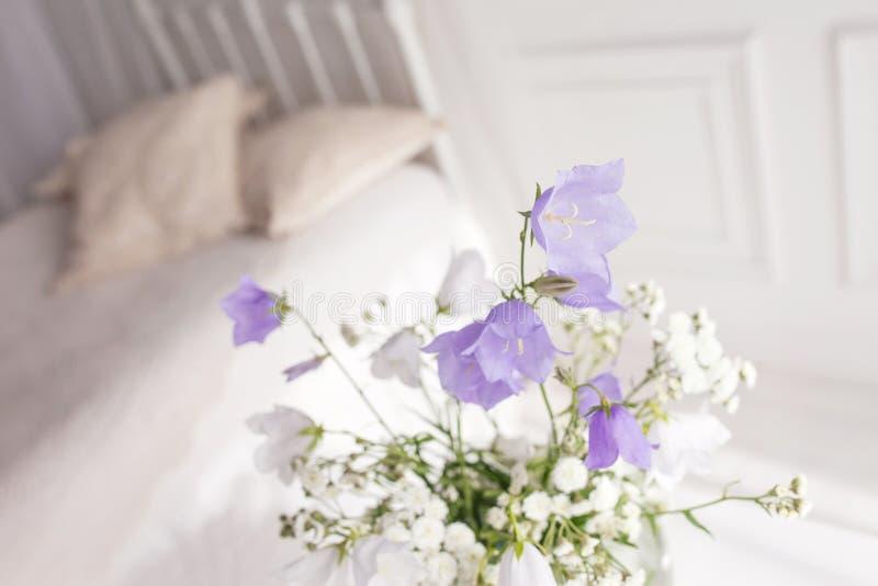Βάζο γυαλιού με τα ιώδη και άσπρα floweers στο ελαφρύ άνετο εσωτερικό κρεβατοκάμαρων Άσπρος τοίχος, κρεβάτι με το άσπρο λινό, ελα στοκ εικόνες με δικαίωμα ελεύθερης χρήσης