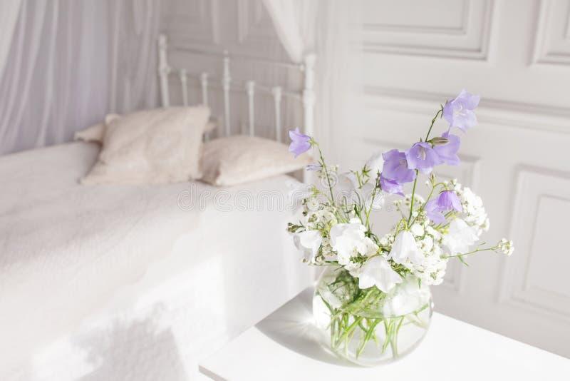 Βάζο γυαλιού με τα ιώδη και άσπρα floweers στο ελαφρύ άνετο εσωτερικό κρεβατοκάμαρων Άσπρος τοίχος, κρεβάτι με το άσπρο λινό, ελα στοκ εικόνα με δικαίωμα ελεύθερης χρήσης