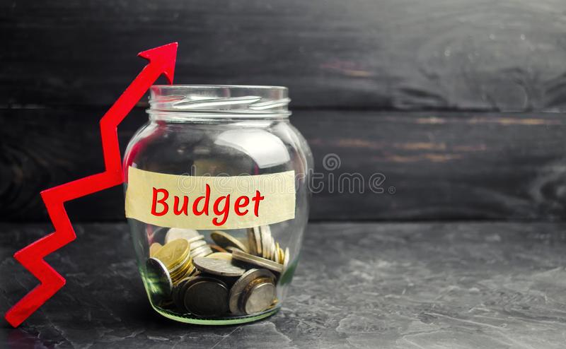 """Βάζο γυαλιού με τα νομίσματα και την επιγραφή """"προϋπολογισμός """"και επάνω στο βέλος Έννοια της επιχειρησιακής επιτυχίας, της οικον στοκ εικόνες"""