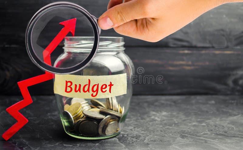 """Βάζο γυαλιού με τα νομίσματα και την επιγραφή """"προϋπολογισμός """"και επάνω στο βέλος Έννοια της επιχειρησιακής επιτυχίας, της οικον στοκ εικόνα με δικαίωμα ελεύθερης χρήσης"""