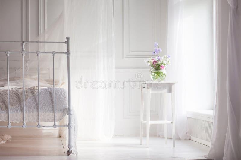 Βάζο γυαλιού με τα ρόδινα και άσπρα floweers στο ελαφρύ άνετο εσωτερικό κρεβατοκάμαρων Άσπρος τοίχος, κρεβάτι με το άσπρο λινό, ε στοκ φωτογραφία