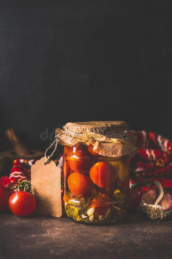 Βάζο γυαλιού με τις κατ' οίκον κονσερβοποιημένες ντομάτες στο σκοτεινό πίνακα Σπιτική αποθήκευση συγκομιδών r r στοκ φωτογραφίες