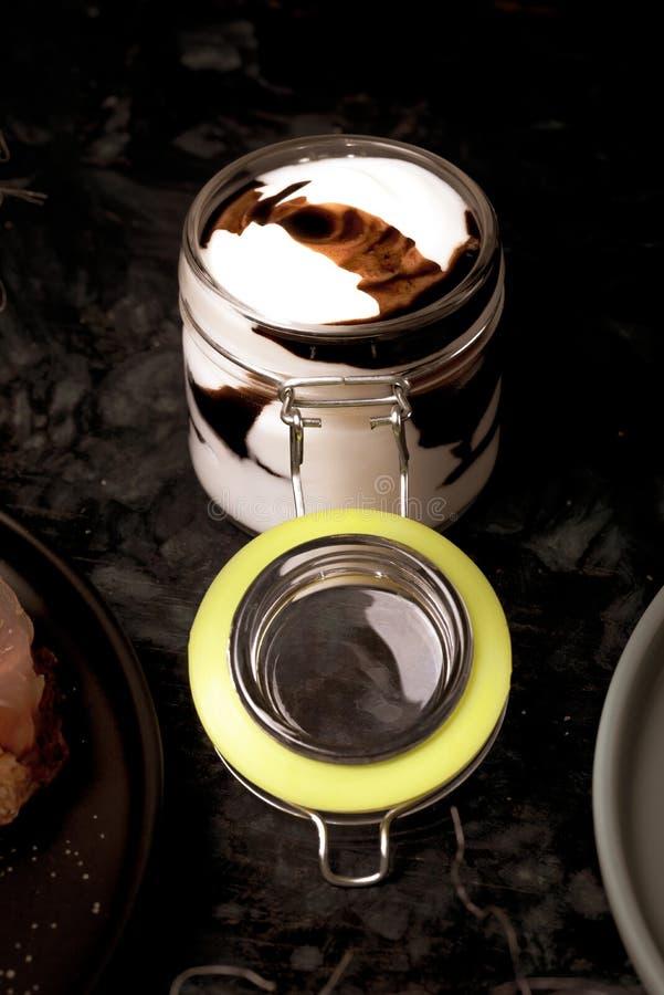Βάζο γυαλιού με το σύνολο κάλυψης της άσπρης και καφετιάς σάλτσας στο σκοτεινό ξύλινο πίνακα στοκ εικόνα