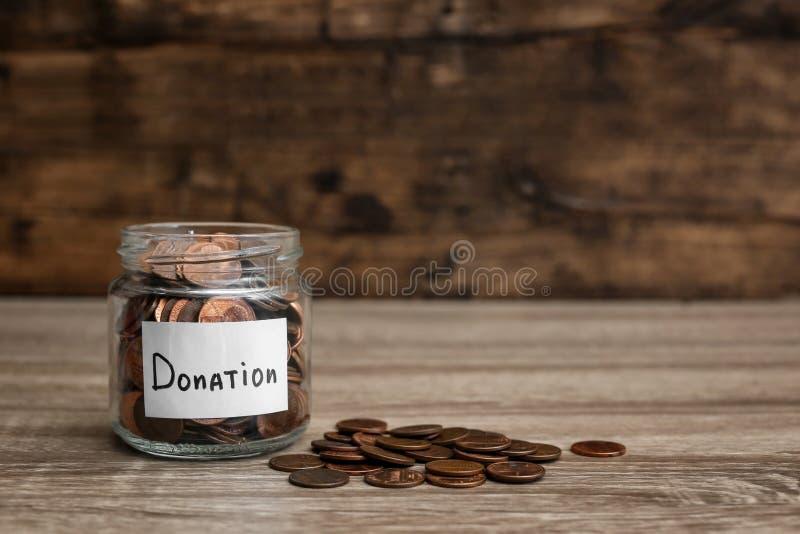 Βάζο και νομίσματα δωρεάς στον πίνακα στοκ εικόνες