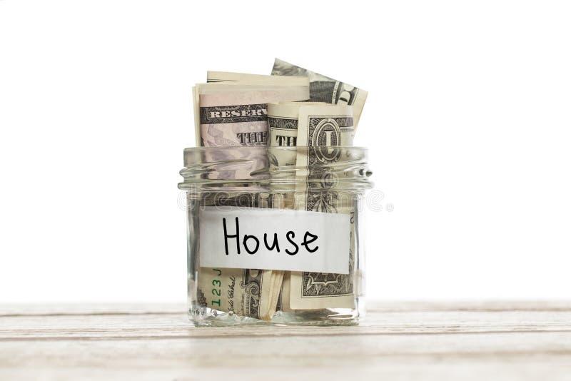 Βάζο με τα χρήματα για τις πληρωμές σπιτιών ή υποθηκών στον ξύλινο πίνακα που απομονώνεται στοκ εικόνες με δικαίωμα ελεύθερης χρήσης