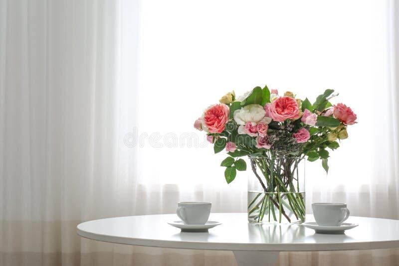 Βάζο με την όμορφη ανθοδέσμη λουλουδιών και φλιτζάνια του καφέ στον πίνακα στο δωμάτιο Διάστημα για στοκ φωτογραφίες