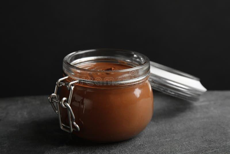 Βάζο με τη νόστιμη κρέμα σοκολάτας στον πίνακα ενάντια στο σκοτάδι στοκ φωτογραφία με δικαίωμα ελεύθερης χρήσης