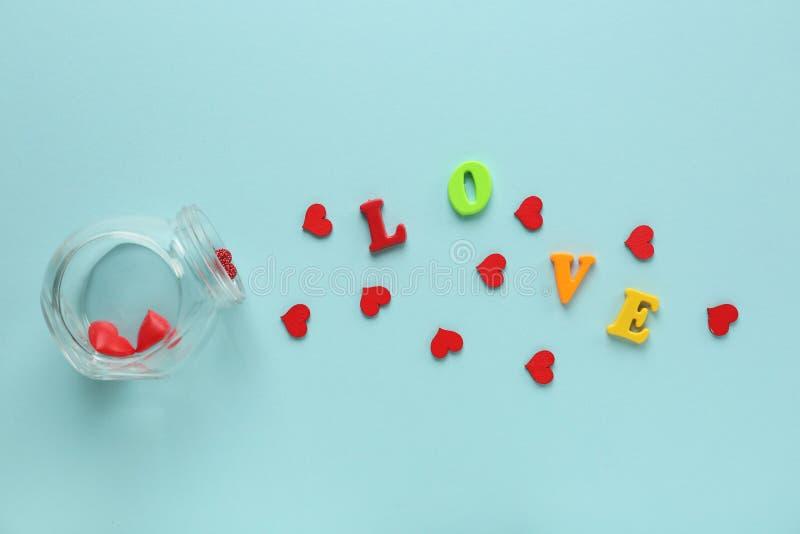 Βάζο με τις διεσπαρμένες καρδιές και ΑΓΑΠΗ λέξης στο υπόβαθρο χρώματος στοκ εικόνες