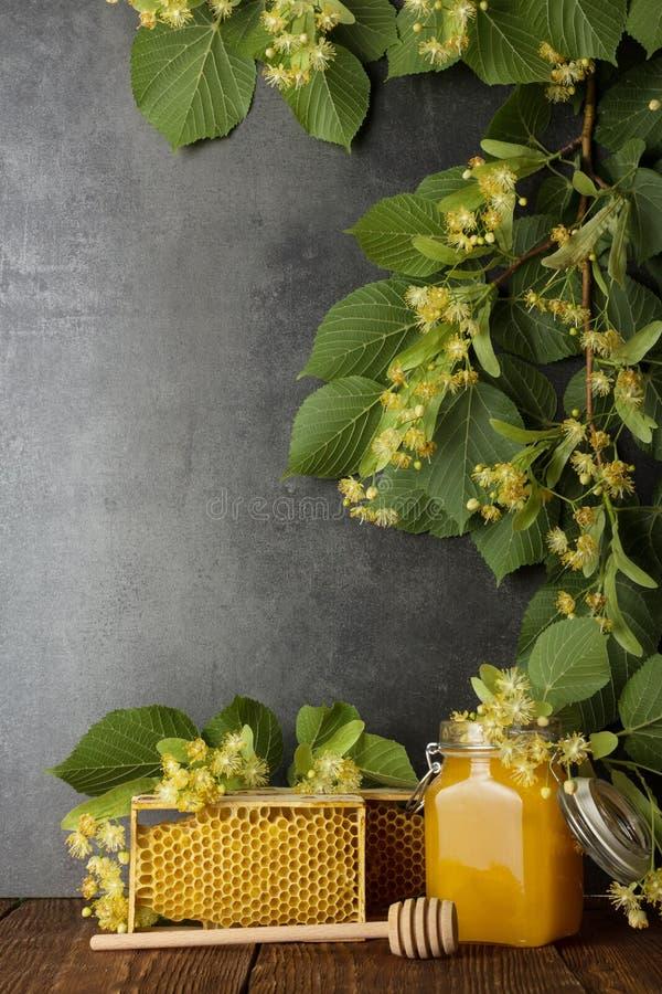 Βάζο με το μέλι, την κηρήθρα και τον αναδευτήρα στο γκρίζο υπόβαθρο, πάνω από τον κλάδο Linden στοκ φωτογραφία με δικαίωμα ελεύθερης χρήσης