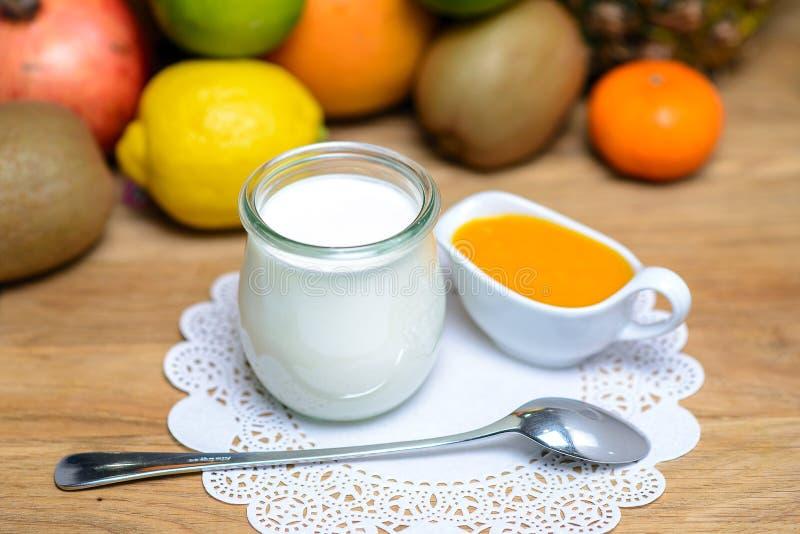 Βάζο του γάλακτος και μια κατσαρόλλα με το μέλι σε ένα υπόβαθρο των τροπικών φρούτων στοκ εικόνες με δικαίωμα ελεύθερης χρήσης