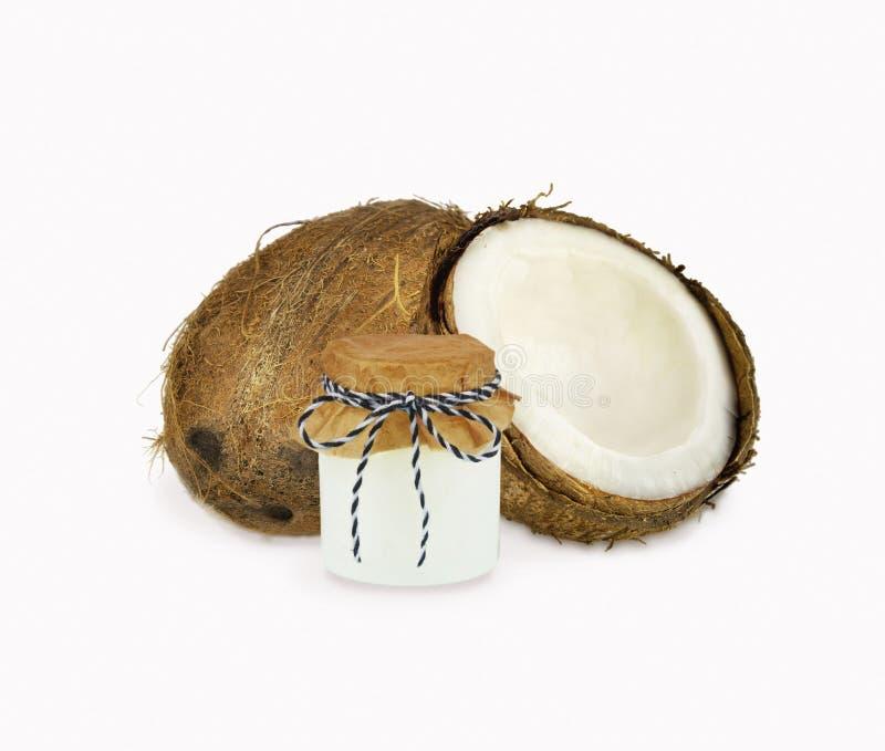 Βάζο του ελαίου καρύδων και των φρέσκων καρύδων που απομονώνονται στο λευκό στοκ φωτογραφία