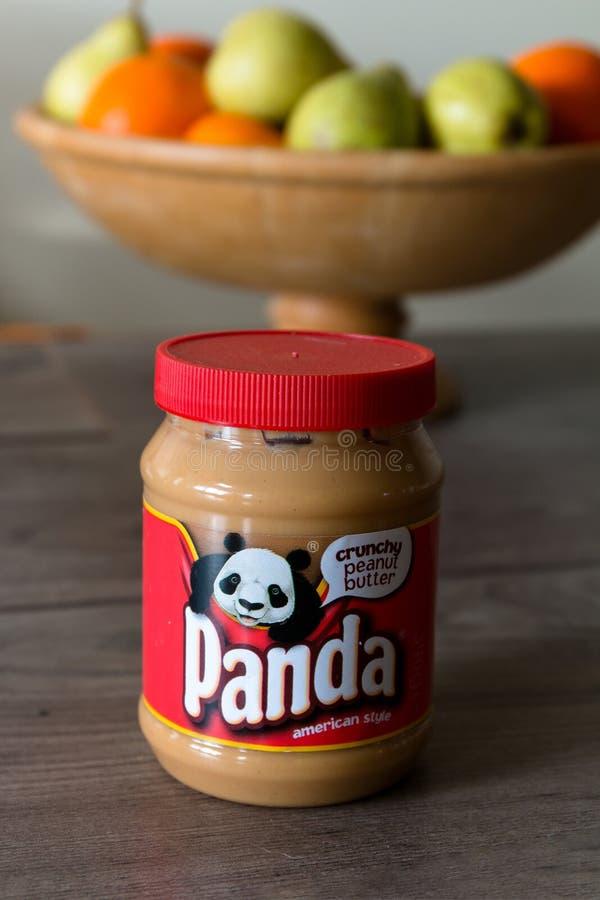 Βάζο φυστικοβουτύρου της Panda πάνω από έναν ξύλινο πίνακα με τα υγιή φρούτα στο υπόβαθρο στοκ εικόνες