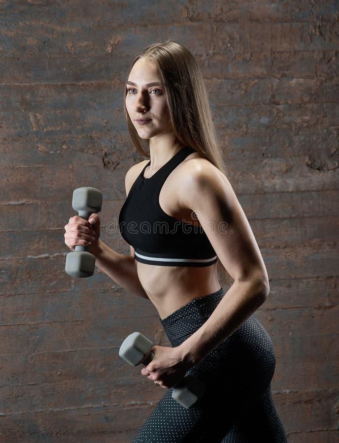 Βάναυση αθλητική γυναίκα που αντλεί επάνω τους μυς με τους αλτήρες στοκ εικόνες με δικαίωμα ελεύθερης χρήσης