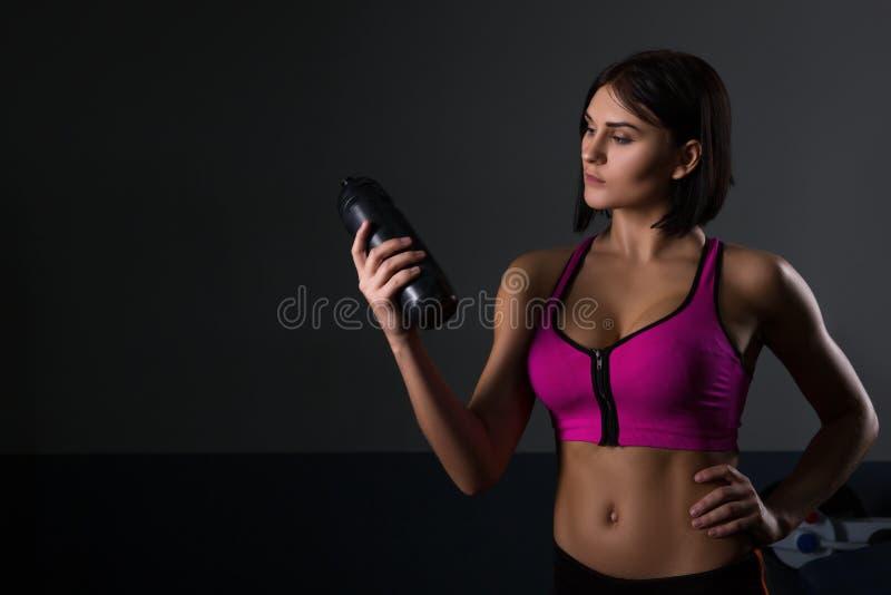 Βάναυση αθλητική γυναίκα που αντλεί επάνω τους μυς με τους αλτήρες στοκ εικόνα