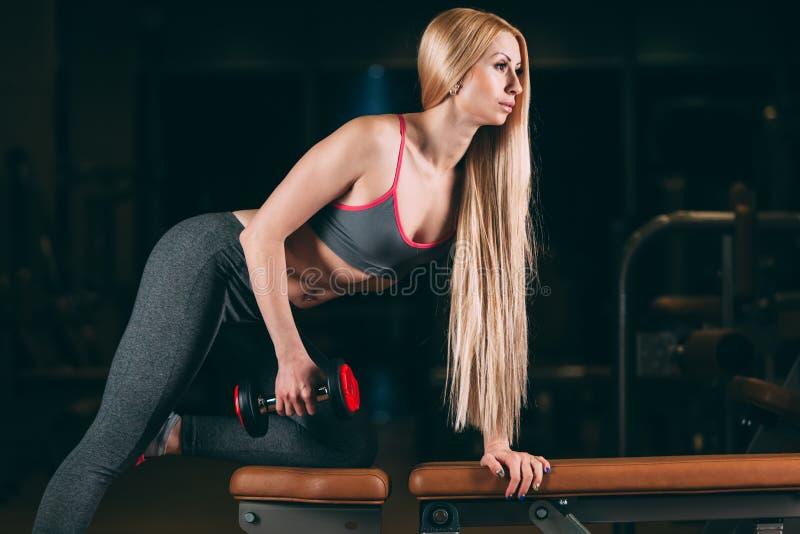 Βάναυση αθλητική γυναίκα που αντλεί επάνω τους μυς με τους αλτήρες στη γυμναστική στοκ φωτογραφία