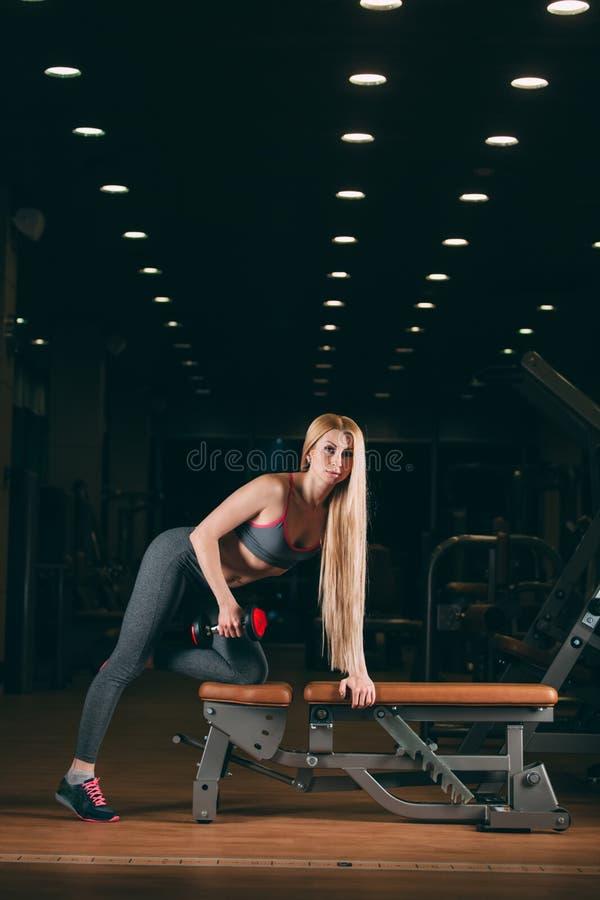 Βάναυση αθλητική γυναίκα που αντλεί επάνω τους μυς με τους αλτήρες στη γυμναστική στοκ εικόνες