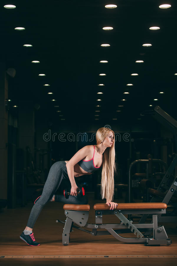 Βάναυση αθλητική γυναίκα που αντλεί επάνω τους μυς με τους αλτήρες στη γυμναστική στοκ φωτογραφίες