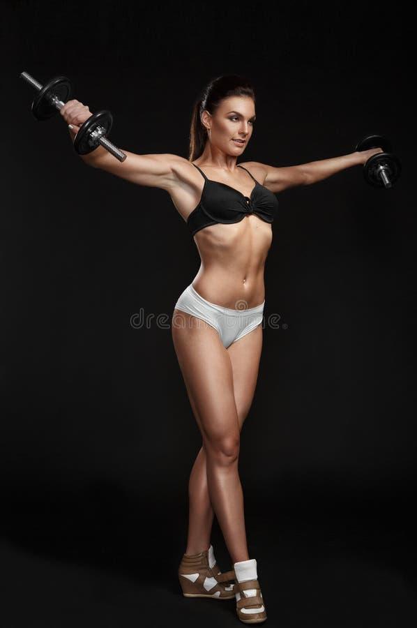 Βάναυση αθλητική γυναίκα που αντλεί επάνω τους μυς με τους αλτήρες στοκ φωτογραφίες με δικαίωμα ελεύθερης χρήσης