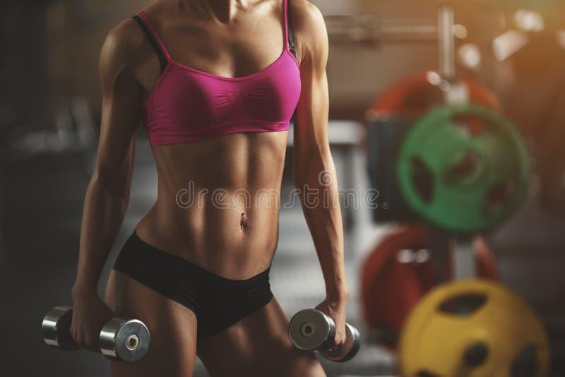 Βάναυση αθλητική γυναίκα που αντλεί επάνω τους μυς με στοκ εικόνες
