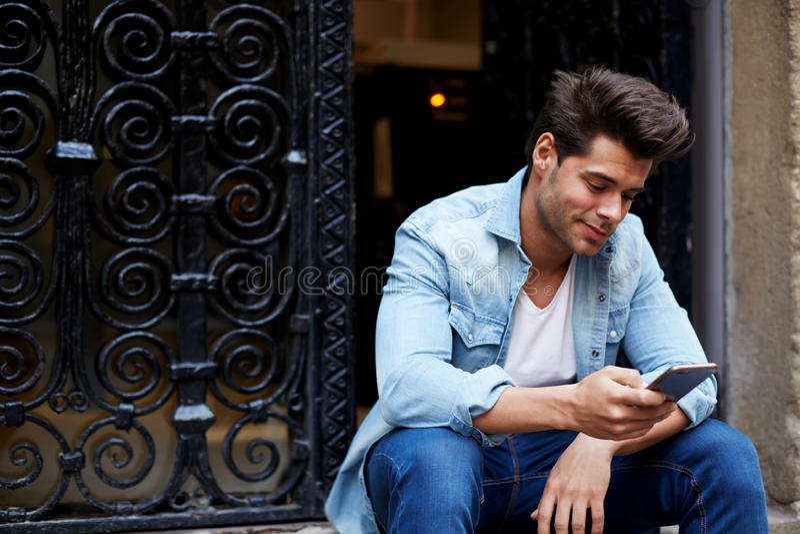 Βάναυση συνεδρίαση νεαρών άνδρων στα βήματα, και προσποιητά χαμόγελα κατά την ανάγνωση ενός μηνύματος στοκ εικόνες