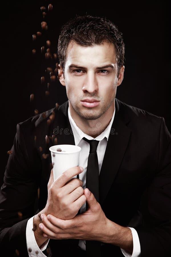 Βάναυσος τύπος σε ένα μαύρο κοστούμι με τον καφέ στοκ εικόνα με δικαίωμα ελεύθερης χρήσης