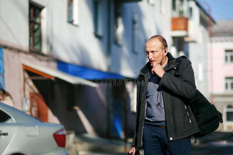 Βάναυσος φωτογράφος οδών με τις διαθέσιμες strolling οδούς πόλεων καμερών, που μιλούν walkie-talkie με ελεύθερα χέρια στοκ φωτογραφία