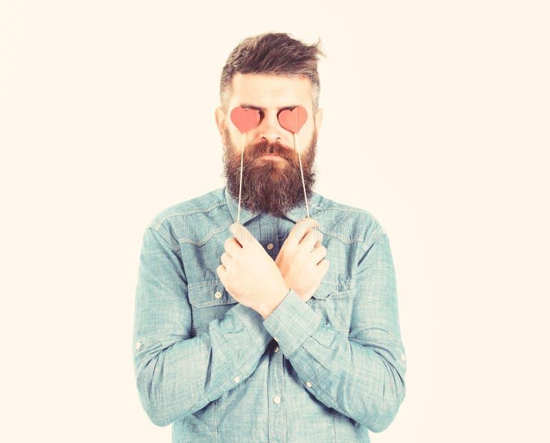 Βάναυσο άτομο ερωτευμένο Τυφλός από την αγάπη Hipster με τις κόκκινες καρδιές εγγράφου και το σοβαρό πρόσωπο Το γενειοφόρο άτομο  στοκ εικόνα