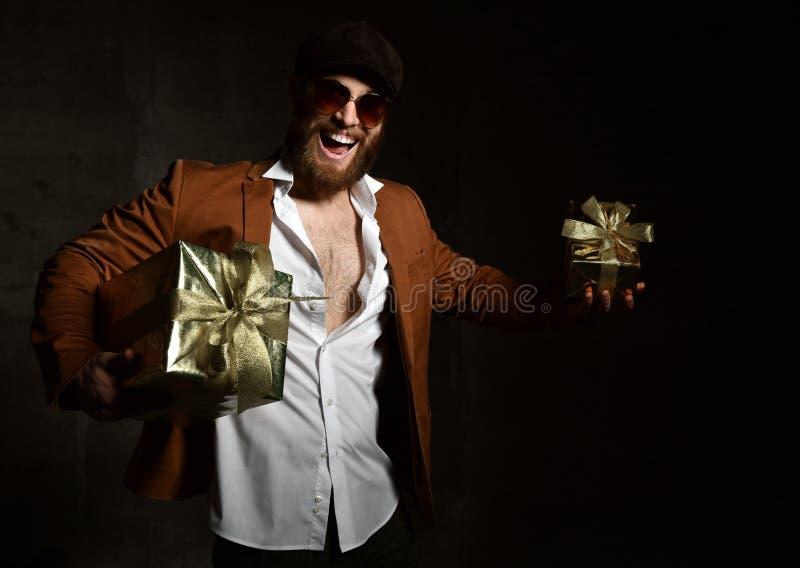 Βάναυσο άτομο με τη γενειάδα και mustache με το χρυσό παρόν δώρο για το γέλιο χαμόγελου γενεθλίων ή Χριστουγέννων στοκ εικόνες