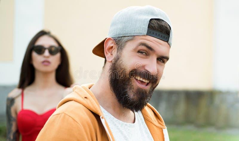 Βάναυσο άτομο με τη μακριά γενειάδα και mustache Μόδα οδών Hipster Ελκυστικός τύπος μπροστά από το κορίτσι Βέβαιος με δικούς του στοκ εικόνες με δικαίωμα ελεύθερης χρήσης