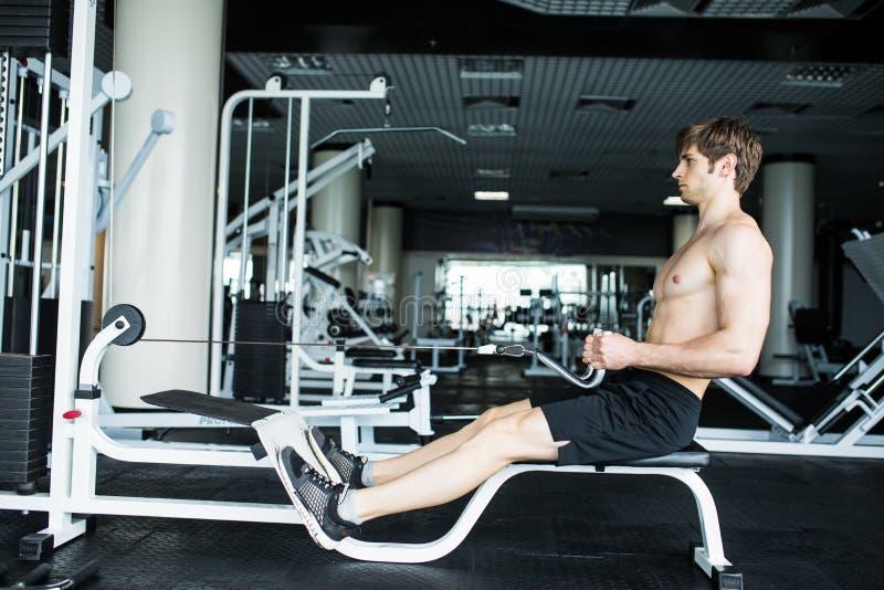 Βάναυσο αθλητικό άτομο που αντλεί επάνω τους μυς στη διασταύρωση Μυϊκό άτομο που επιλύει στη γυμναστική που κάνει τις ασκήσεις γυ στοκ φωτογραφίες
