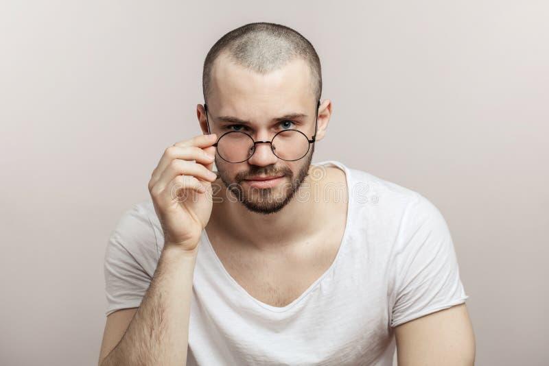 Βάναυσο γενειοφόρο αρσενικό που φορά γύρω από τα γυαλιά, που ντύνονται άνετα, στοκ φωτογραφία με δικαίωμα ελεύθερης χρήσης