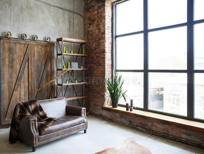 Βάναυσο εσωτερικό σε ένα σκοτεινό καφετί χρώμα με έναν καναπέ δέρματος και ένα μεγάλο παράθυρο στοκ εικόνες