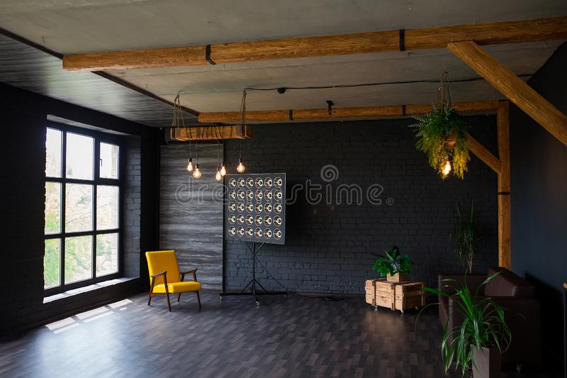 Βάναυσο σύγχρονο εσωτερικό σε ένα σκοτεινό χρώμα με έναν καναπέ δέρματος και ένα μεγάλο παράθυρο Καθιστικό ύφους σοφιτών στοκ φωτογραφίες με δικαίωμα ελεύθερης χρήσης