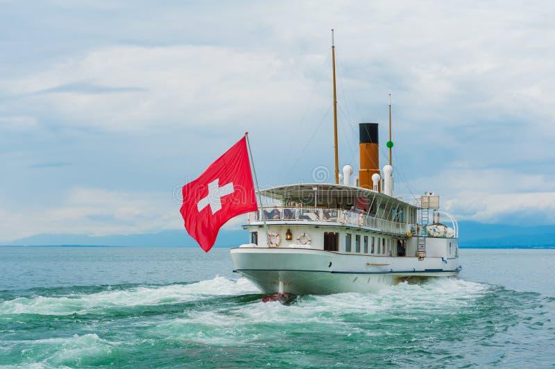 Βάρκα ατμού με την ελβετική σημαία που επιπλέει στη λίμνη στοκ εικόνες