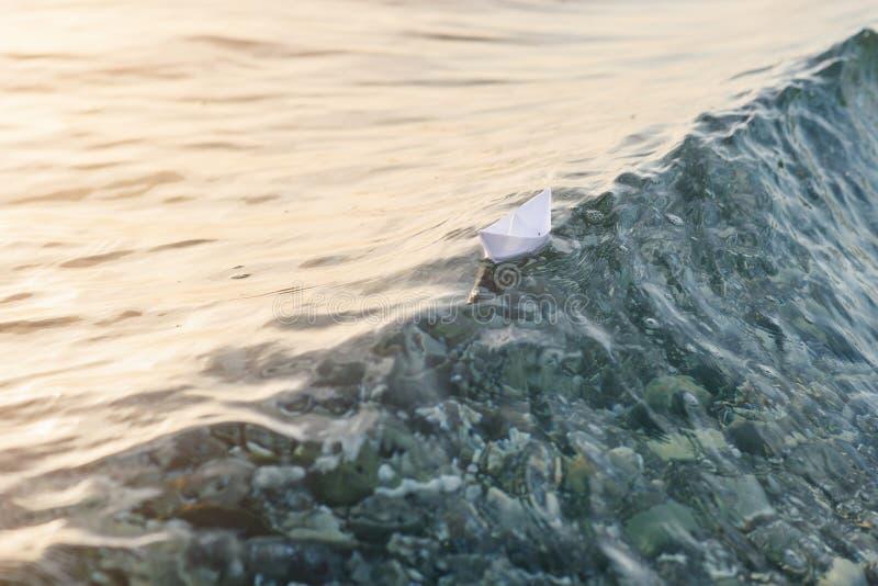 Βάρκα εγγράφου που πλέει με το λόφο των κυμάτων στη θάλασσα στοκ φωτογραφία με δικαίωμα ελεύθερης χρήσης