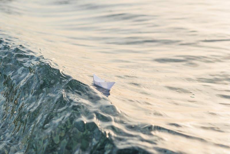 Βάρκα εγγράφου που πλέει με το λόφο των κυμάτων στη θάλασσα στοκ εικόνες